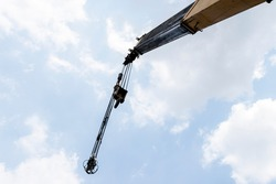 Yellow crane boom with hooks and blue sky background