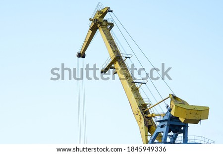 Yellow crane in cargo port translating coal. Industrial scene stock photo