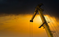 Yellow crane in cargo port translating coal. Industrial scene. Cargo crane at sunset