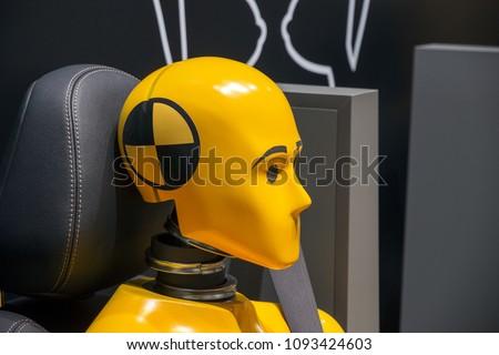 Yellow crash test dummy in a car seat.