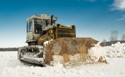 Yellow crawler tractor bulldozer with a bucket works in winter clearing the road from snow. Frosty day with bright sun and beautiful blue sky in the background. Yellow bulldozer in winter.