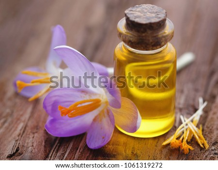 Yellow Crocus or Saffron with essential oil in a bottle on natural surface