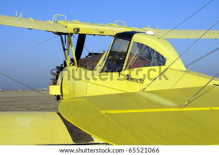 Yellow crop duster biplane with spray nozzles mounted on wing trailing edge