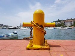Yellow cruciform steel bitts with the sea in the background on the Acapulco boardwalk, Mexico