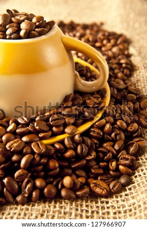 Yellow cup of   coffee beans