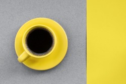 Yellow cup of coffee on a gray background. Demonstration of gray and yellow colors trendy colors 2021.