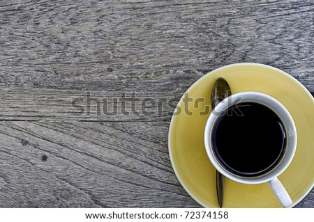 Yellow cup of coffer over the old wood