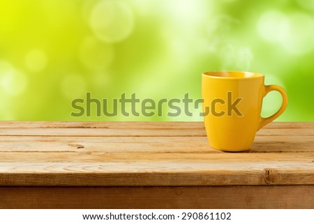 Yellow cup on wooden table over green bokeh background