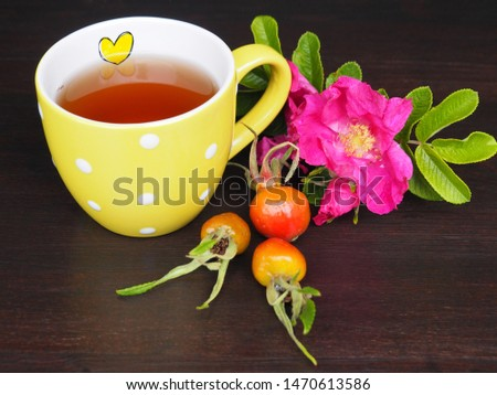 Yellow Cup with heart, healthy tea, rose hips and rose flower on a dark background large. Beautiful and bright picture of the national wide recipe of medicinal tincture for health.