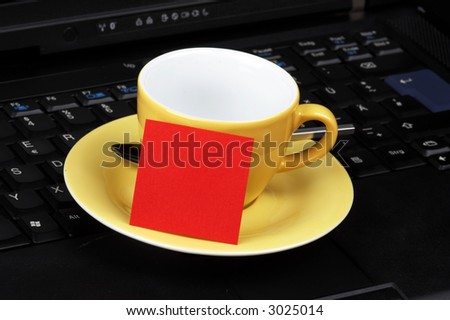 yellow cup with red post-it on black laptop