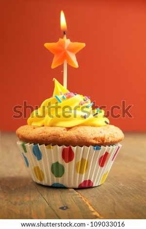 Yellow cupcake with star birthday candle on a wooden table