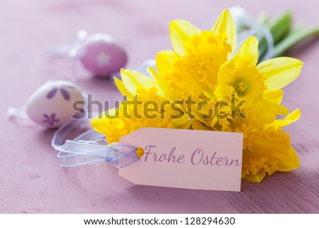 yellow daffodils with tag and german text Frohe Ostern