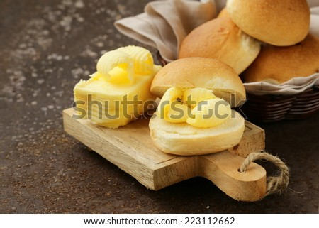 yellow dairy butter on a fresh bun bread for breakfast