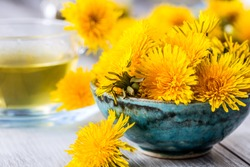 Yellow dandelion heads in bowl or table.