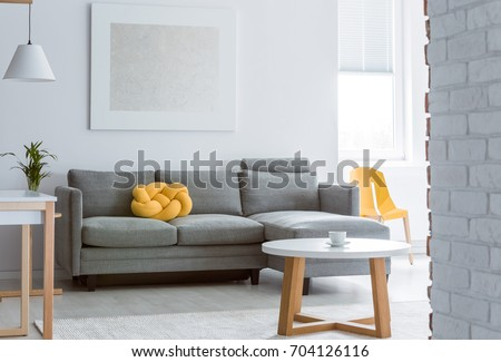 Yellow decorative pillow on grey sofa in living room with brick white wall and simple coffee table