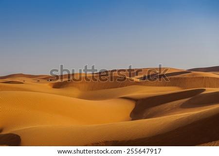 Yellow desert dunes and sky.