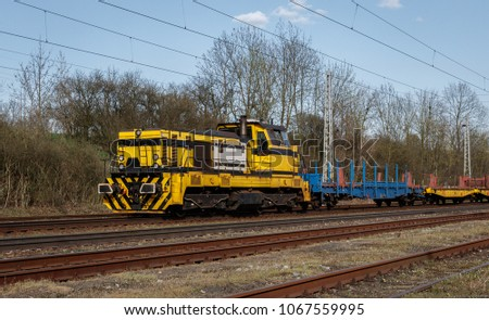 Yellow diesel electric shunting locomotive (switcher, shifter) in head of cargo (freight) train.
