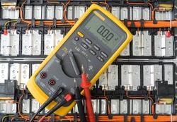 Yellow Digital multimeter with probes on Lithium ion battery background , A multimeter is an electronic measuring instrument, Technology concept