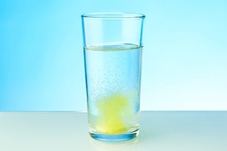 yellow dissolving pill dissolves in water on colored background. a glass of water and an effervescent vitamin pill. the medicine tablet dissolves in a glass of water