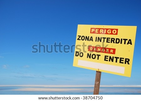 yellow do not enter sign on a dangerous zone at the beach