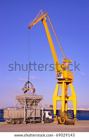Yellow dock crane unloading material from a cargo ship