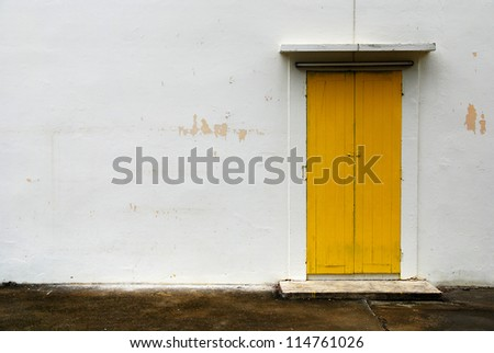 Yellow door and white wall - stock photo
