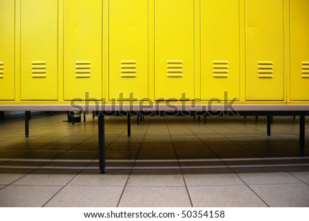 Yellow doors in a locker room and a bench - stock photo