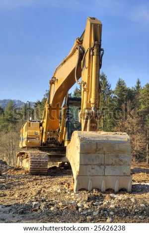 Yellow dredger on construction ground against forest and sky.
