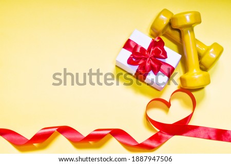 Yellow Dumbbells, gift box and red ribbon in the form of a heart on a yellow background. Top view, copy space. Flat lay. Valentine's Day card. Fitness, sport and healthy lifestyle concept.  ストックフォト ©