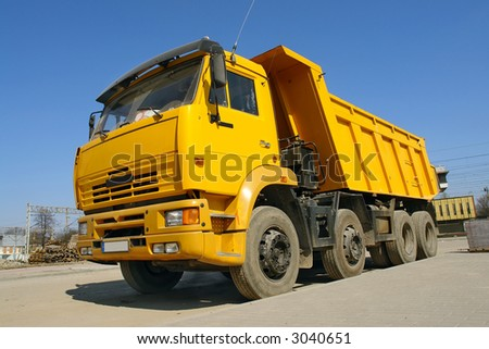 Yellow dump truck parked against clear blue sky