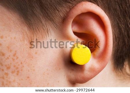 yellow earplug into the ear close up - stock photo
