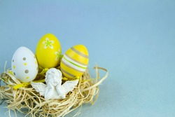 Yellow easter eggs in a nest with angel on a blue background