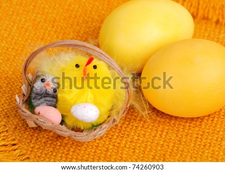 Yellow easter eggs with decorative chickens in basket.
