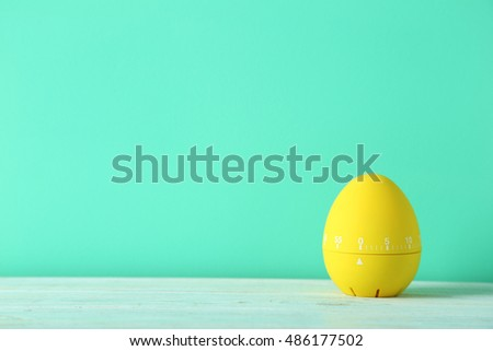 Yellow egg timer on green wooden background