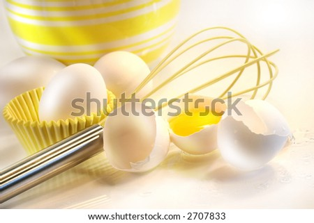 Yellow egg yolk with eggs and whisk for baking