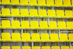Yellow empty seats for fans on football tribune