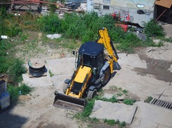 Yellow excavator (digger, bagger) on the construction site