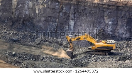 Yellow excavator digging for ore rich rock in an open pit mine
