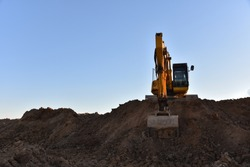 Yellow excavator during earthmoving at open pit on blue sky background. Construction machinery and earth-moving heavy equipment for excavation, loading, lifting and hauling of cargo on job sites
