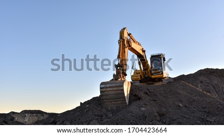 Photo of  Yellow excavator during earthmoving at open pit on blue sky background. Construction machinery and earth-moving heavy equipment for excavation, loading, lifting and hauling of cargo on job sites