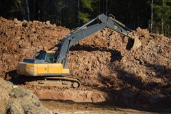 Yellow excavator during earthworks in an open pit against the background of forest and soil. Construction machinery and earth moving heavy machinery for excavation, loading, lifting and transporting l
