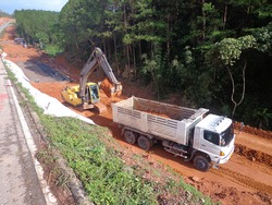 Yellow excavator is filling a dump truck with soil