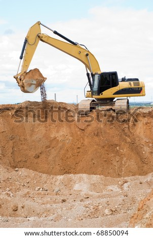 Yellow excavator loader at construction site with raised bucket full of sand - stock photo