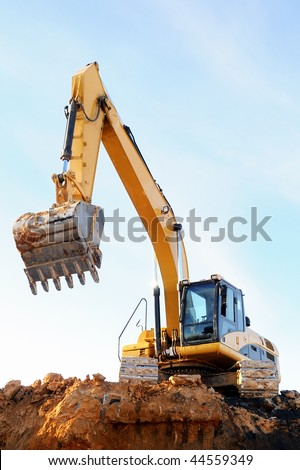 Yellow excavator loader at construction site with raised bucket over blue sky