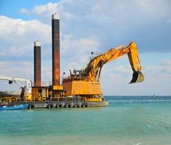 Yellow excavator machine construct sea defences on the beach
