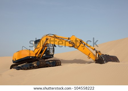 Yellow excavator on a sand dune