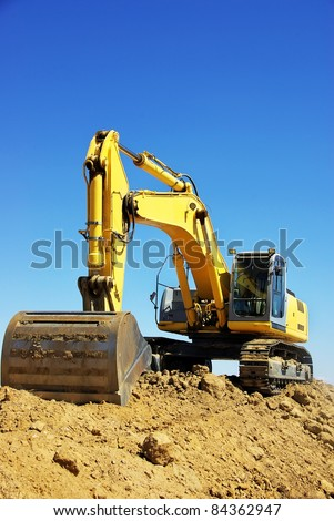 Yellow excavator on a working platform