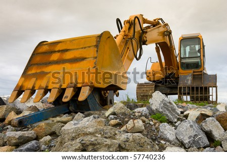 yellow excavator on top of big heap of stones, close up