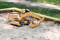 Yellow excavator toy in wooden sandbox at yard. Boy's toys concept