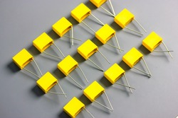 Yellow film capacitors isolated on gray background top view. Many square shape plastic electronic radio components on the gray surface with contrast shadows flatly. Selective focus.